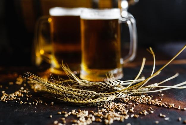 Copos de cerveja e especiarias de trigo em uma velha mesa de madeira rústica em fundo preto