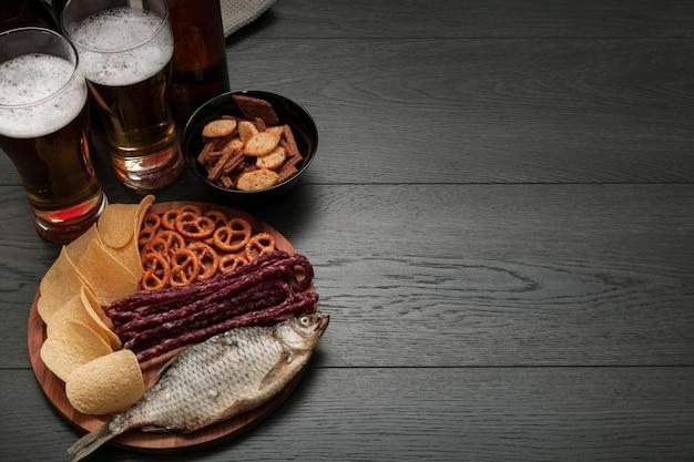 Copos de cerveja e prato de comida com espaço de cópia