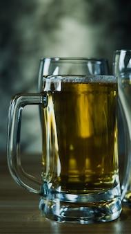 Copos de cerveja escura, cerveja gelada artesanal em copo na mesa de madeira