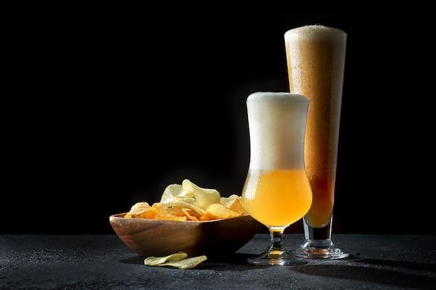 Copos de cerveja escura e clara com batatas fritas