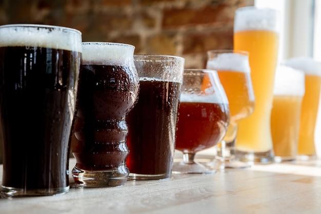 Copos de cerveja escura e clara e cerveja à luz do sol na parede de tijolos.