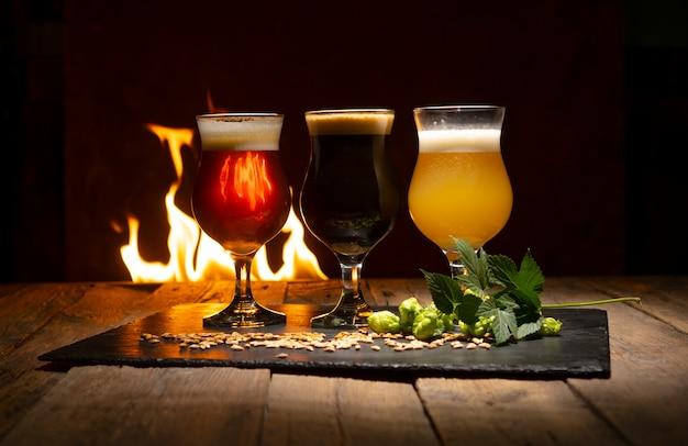 Copos de cerveja, galho de lúpulo, grão de trigo na rústica mesa de madeira contra o fogo