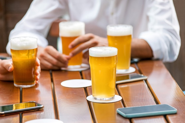 Copos de cerveja gelada com cabeças espumosas em uma mesa de bar ao lado das mãos de um grupo de amigos em um encontro relaxante