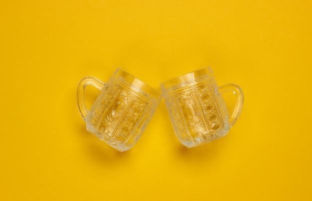Copos de cerveja lapidados retrô vazios em um fundo amarelo. vista do topo