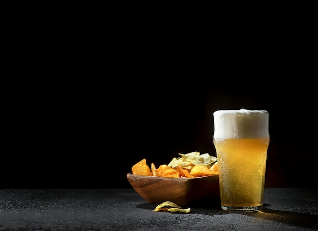 Copos de cerveja light com batatas fritas no escuro