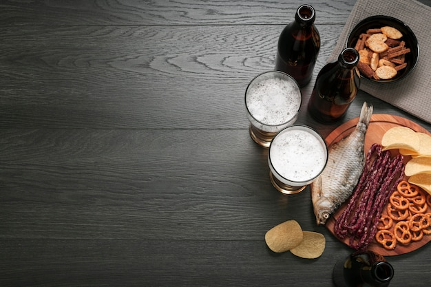 Copos de cerveja plana leigos e prato de comida com espaço de cópia