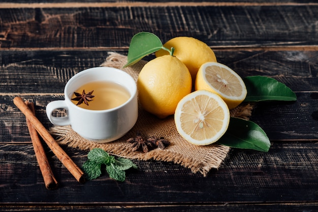 Copos de chá com limão, limões cortados em uma tábua de cortar