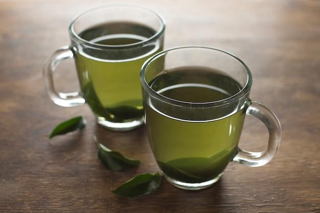 Copos de chá de ervas verde limão na mesa de madeira