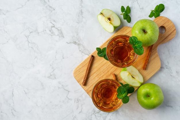 Copos de chá saudável de maçã verde colocados ao lado de maçãs verdes frescas