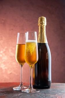 Copos de champanhe com vista frontal e garrafa na luz comemoração festa beber álcool foto cor de ano novo