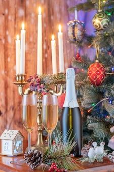 Copos de champanhe e composição de presentes com candelabros acesos.