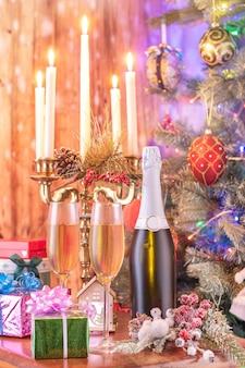 Copos de champanhe e presentes no fundo brilhante com fragmento da árvore de natal e candelabros iluminados.