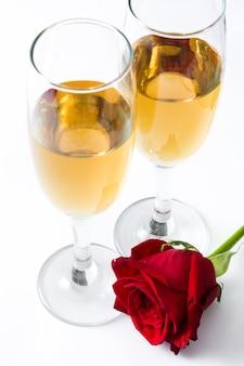 Copos de champanhe e rosa isolado no branco
