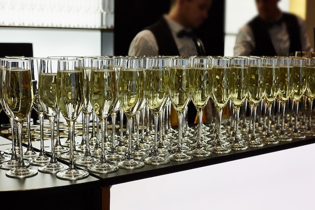 Copos de champanhe estão sobre a mesa. no fundo são dois garçom