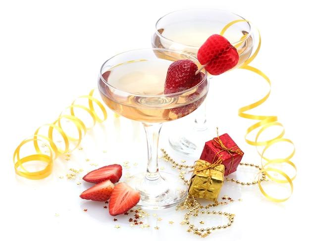 Copos de champanhe, morangos e presentes isolados em um branco