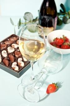 Copos de champanhe ou vinho de uva branca com prato de chocolates e morango, garrafa no fundo.