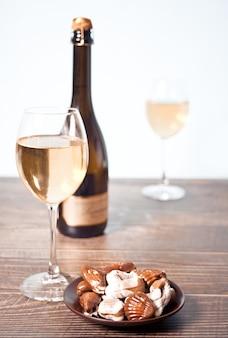 Copos de champanhe ou vinho de uva branca com prato de chocolates, garrafa no fundo.