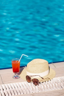 Copos de cocktail e chapéu na margem da piscina