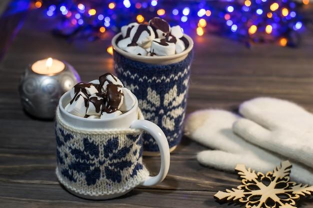 Copos de composição de natal com chocolate quente ou cacau e marshmallows, velas, flocos de neve decorativos e luvas com festão em uma superfície de madeira. vista lateral