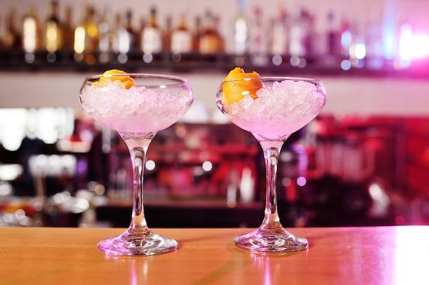 Copos de coquetéis com gelo fechem na superfície do bar