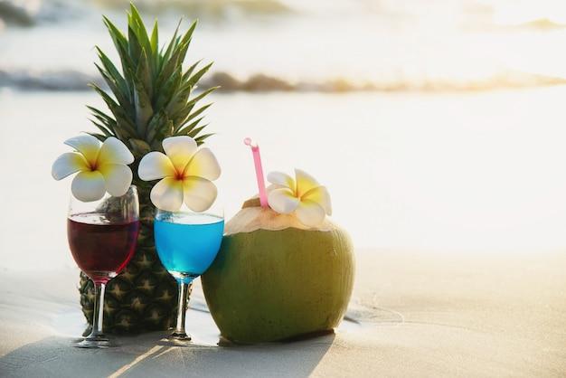 Copos de coquetel com coco e abacaxi na praia de areia limpa - frutas e bebidas na praia do mar