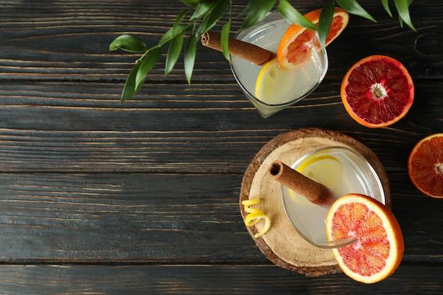 Copos de coquetel com frutas cítricas em fundo de madeira