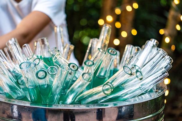 Copos de coquetel tubular e mocktail estão juntos em um balde de aço inoxidável com a bebida turquesa dentro.