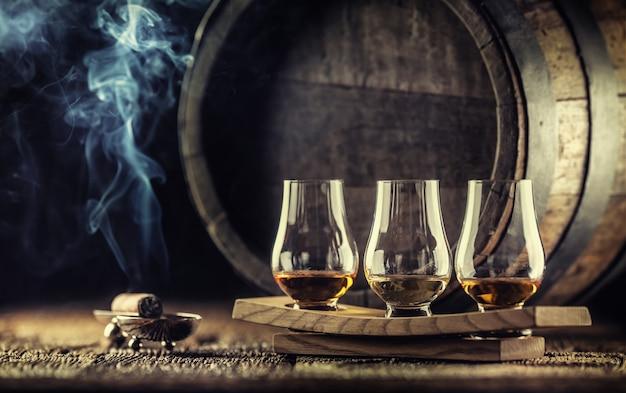 Copos de degustação de uísque glencairn em uma porção de madeira, com um barril de uísque no fundo escuro e um charuto fumegante ao lado.