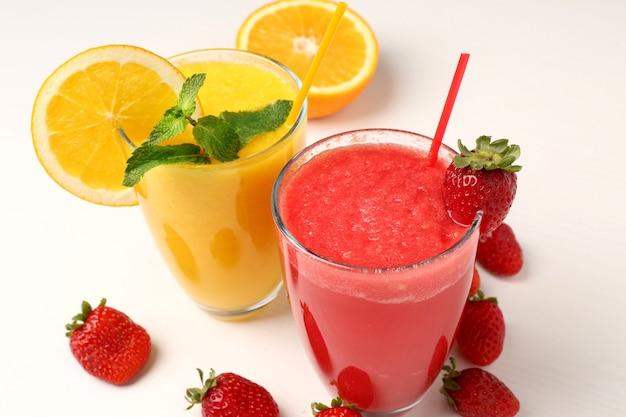 Copos de deliciosos milk-shakes de morango e laranja na mesa de madeira