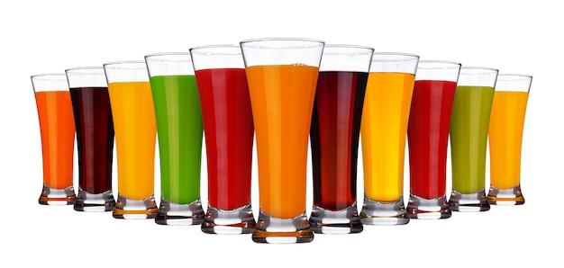 Copos de diferentes sucos de frutas e legumes isolados no branco