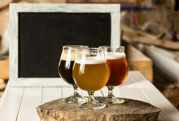 Copos de diferentes tipos de cerveja em fundo de madeira