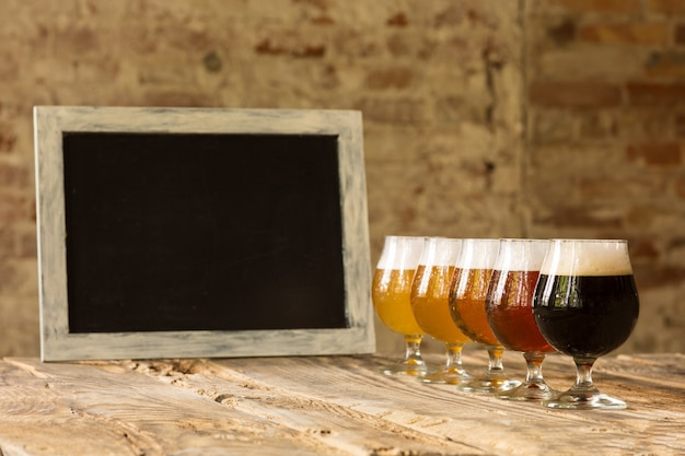 Copos de diferentes tipos de cerveja escura e clara na mesa de madeira em linha e quadro-negro