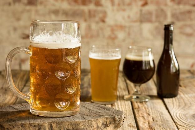 Copos de diferentes tipos de cerveja escura e clara na mesa de madeira em linha.