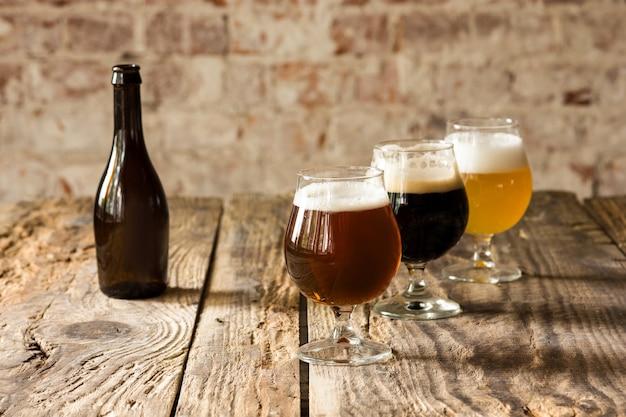 Copos de diferentes tipos de cerveja escura e clara na mesa de madeira em linha