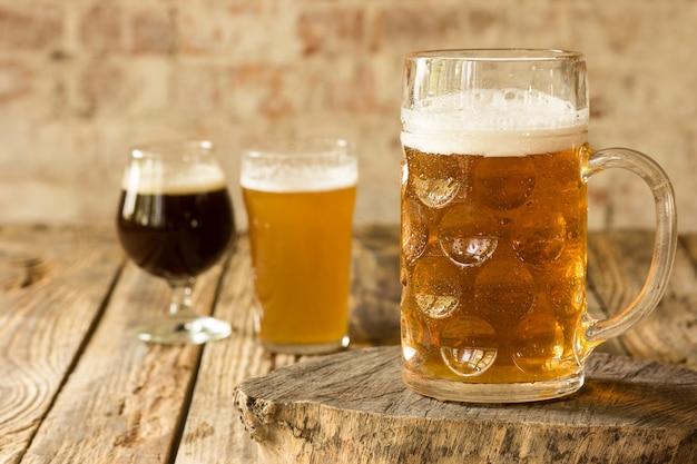 Copos de diferentes tipos de cerveja escura e clara na mesa de madeira