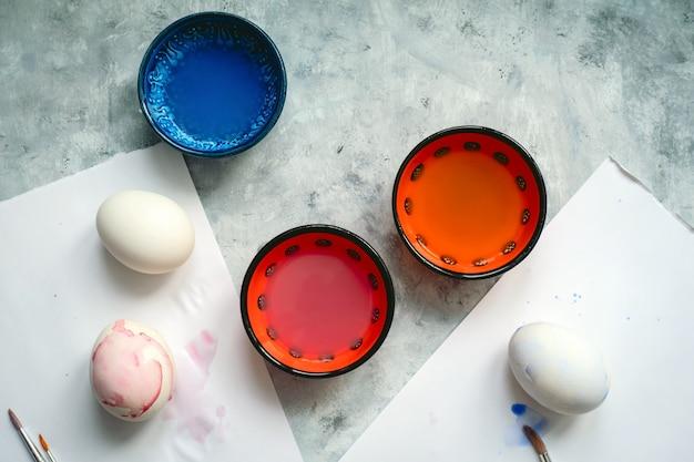 Copos de foco seletivo de vista superior com corante, pincéis e ovos brancos