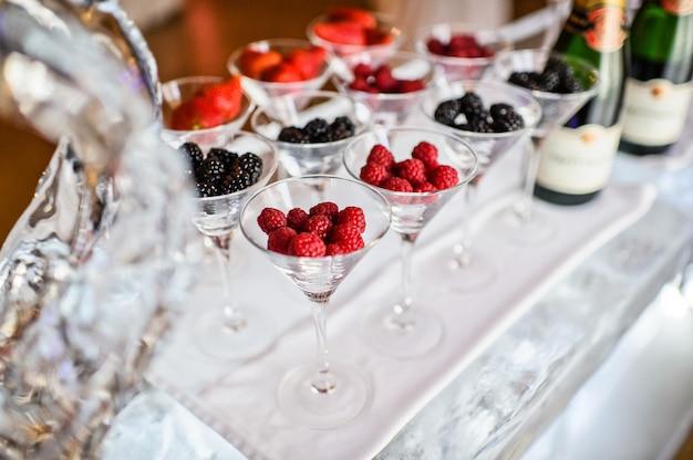 Copos de framboesas, morangos, amoras na barra de gelo. jantar de gala no restaurante.