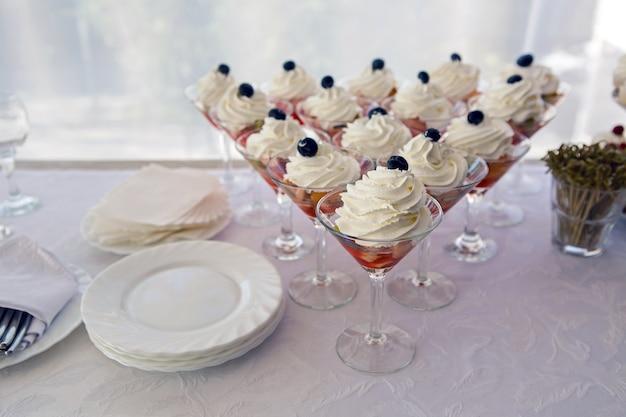 Copos de frutas com creme e frutas vermelhas em cima da sobremesa de mirtilo