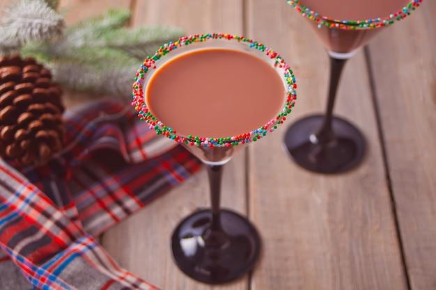 Copos de inverno temporada chocolate cocktail, galho de árvore de natal na madeira