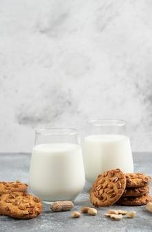 Copos de leite e biscoitos caseiros com amendoim orgânico na mesa de mármore.