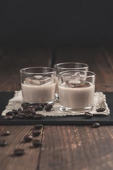 Copos de licor de café creme com gelo e grãos de café na superfície de madeira rústica