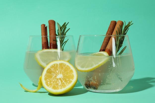 Copos de limonada com canela e alecrim no fundo de hortelã