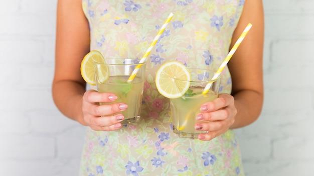 Copos de limonada realizada por uma mulher