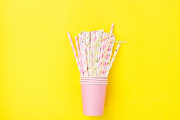 Copos de papel bebendo cor-de-rosa empilhados com palhas listradas no fundo amarelo.