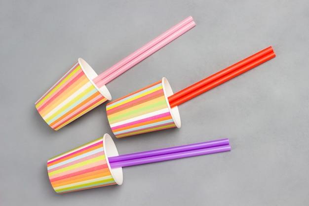 Copos de papel coloridos e canudos plásticos coloridos para bebidas