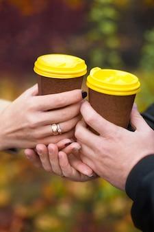 Copos de papel com café / chá / cappuccino / café com leite nas mãos dos amantes