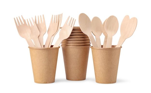 Copos de papel descartáveis com garfos de madeira e colheres isolados no fundo branco. talheres descartáveis ecológicos de material natural.