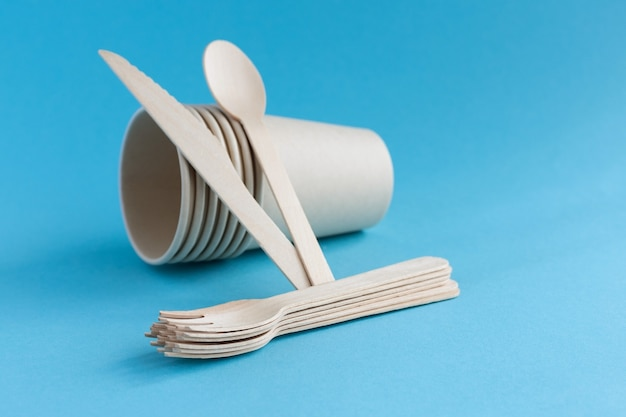 Copos de papel descartáveis ecológicos e talheres feitos de colheres de madeira, garfos e facas em uma superfície azul