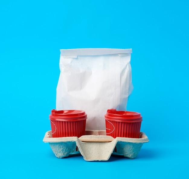 Copos de papel descartáveis vermelhos na bandeja e um saco de papel branco cheio em um espaço azul