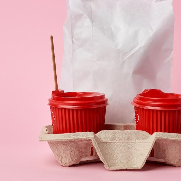 Copos de papel descartáveis vermelhos na bandeja e um saco de papel branco cheio